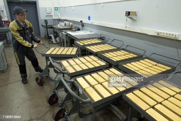 A worker moves trolleys containing 125 kilogram gold ingots ready for distribution at the JSC Krastsvetmet nonferrous metals plant in Krasnoyarsk...
