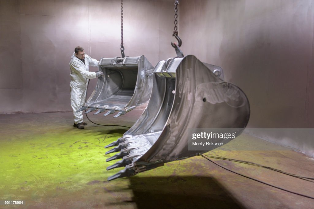 Worker moving digger buckets into spray painting booth in engineering factory : Stock Photo