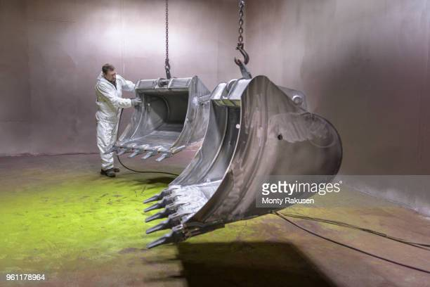 worker moving digger buckets into spray painting booth in engineering factory - monty shadow stock photos and pictures