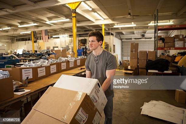 worker moving trolley of cardboard boxes - heshphoto stock pictures, royalty-free photos & images