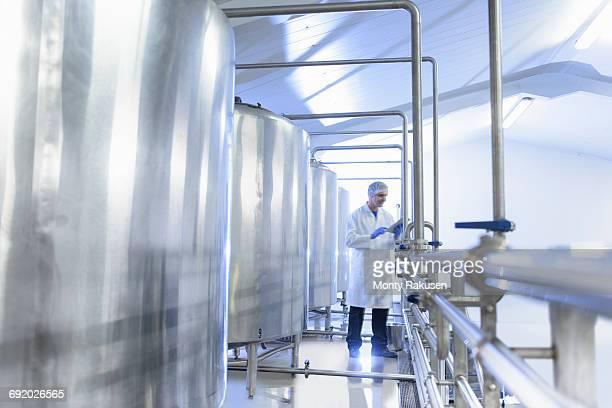 worker next to water tanks in spring water factory - water tower storage tank stock pictures, royalty-free photos & images