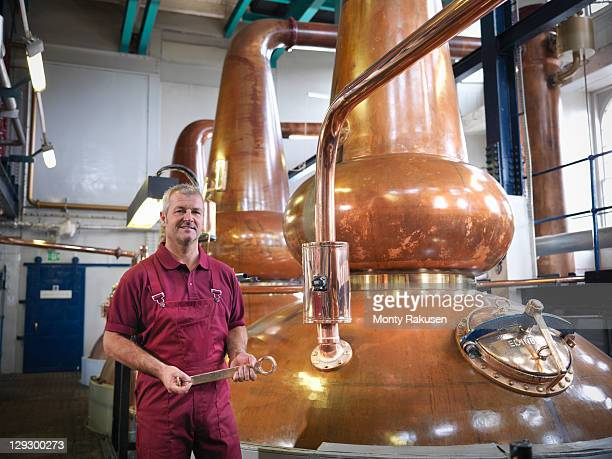 Worker next to whisky stills in distillery