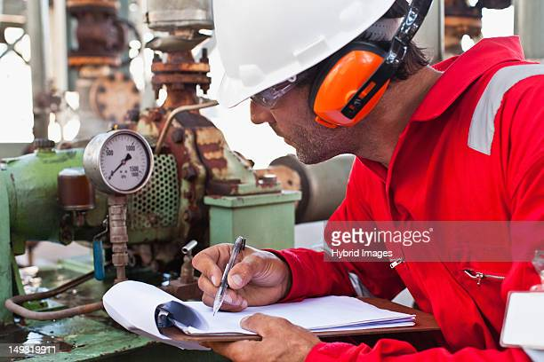 worker noting gauge at oil refinery - gas refinery stock photos and pictures