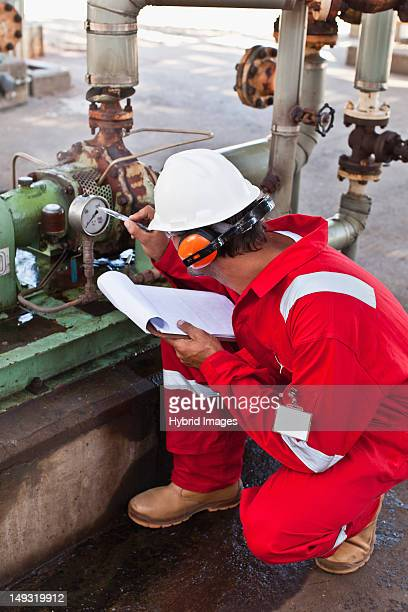 Worker noting gauge at oil refinery