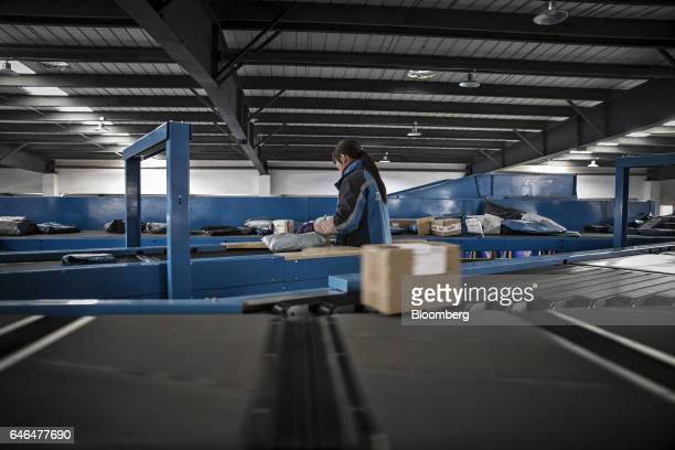 A worker observes packages moving along a conveyor at a ZTO Express Inc sorting facility in Shanghai China on Friday Feb 10 2017 Package delivery...