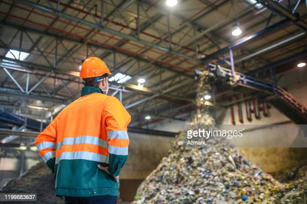 worker observing processing of waste at recycling facility - waste management stock pictures, royalty-free photos & images