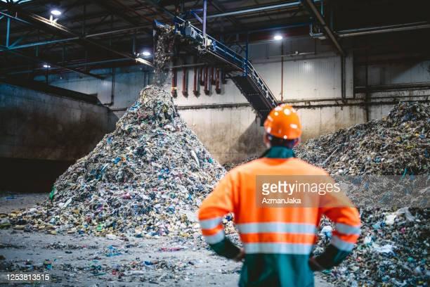 リサイクル施設で廃棄物処理を観察する作業員 - 廃棄物処理 ストックフォトと画像