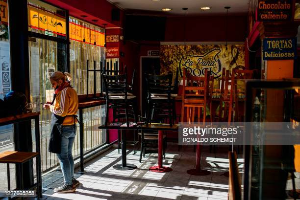 A worker of an empty restaurant is pictured at La Boca neighbourhood in Buenos Aires on July 14 2020 amid the new coronavirus pandemic Buenos Aires'...