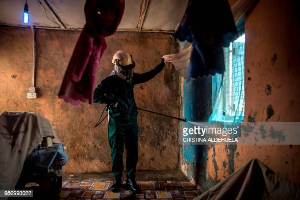 Worker of Anglogold Ashanti Malaria Ltd sprays the walls of a house with insecticide against mosquitos on May 2, 2018 in Adansi Domeabra, near...