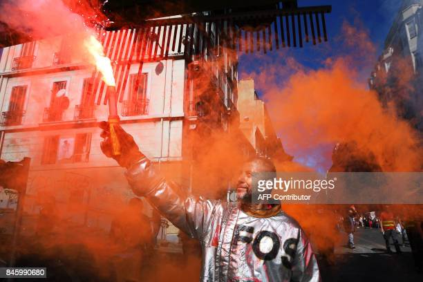 TOPSHOT A worker of ArcelorMittal holds a flare during a protest called by several French unions against the labour law reform in Marseille southern...