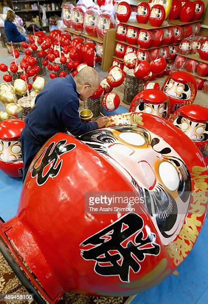 A worker of Daruma factory paints on November 19 2014 in Takasaki Gunma Japan Daruma dolls are lucky charms that people wish their dreams come true...