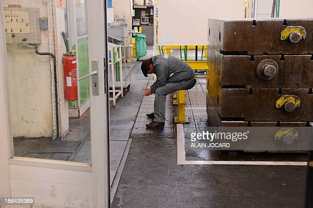 A worker of French automotive supplier Heuliez is seated on October 31 2013 in Cerizay's factory centralwestern France on the last day of the...