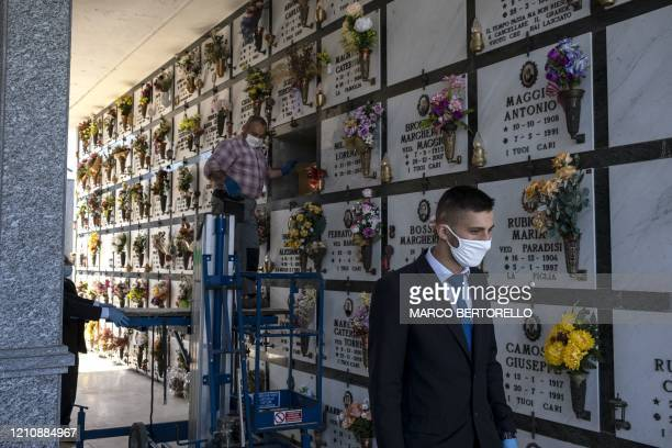 A worker of funeral home company Palmero leaves as an undertaker closes the funeral niche after a funeral service of a victim of COVID19 on April 24...
