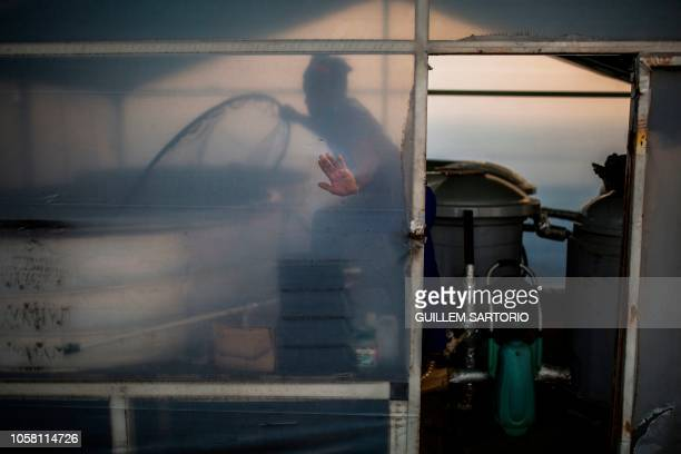 Worker of Rooftops Roots Thulani Shabangu cleans the tanks where water is filtered in Johannesburg on November 2 2018 Rooftop Roots uses methods of...