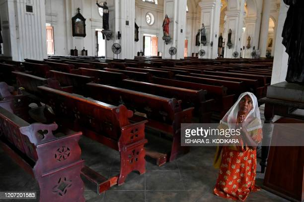 A worker of St Lucia's Cathedral prays on March 15 following the Sri Lanka's Catholic church announcement to call off their masses as a preventive...