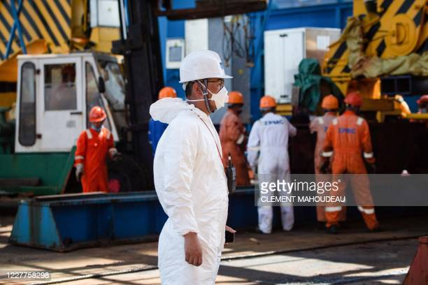 A worker of the Chinese company Shanghai Zhenhua Heavy Industries looks on next to his colleague dismantling the rails used for the unloading of one...