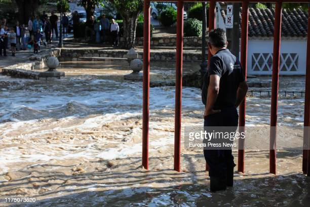 Worker of the City Council of Villar del Olmo and some neighbours are seen next to the river Vega which is overflowing after the heavy rains and...