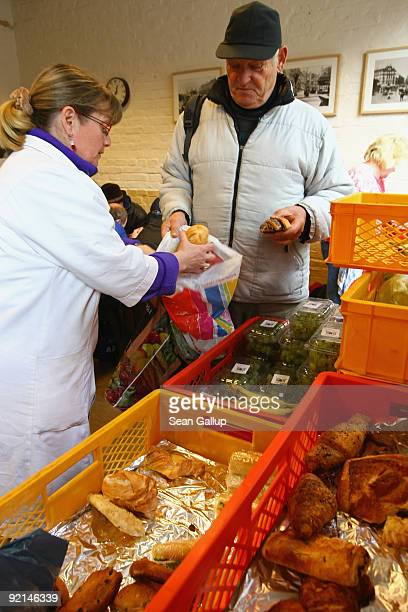 A worker of the Malteser charity part of the Order of Malta Worldwide Relief distributes groceries to the needy at a Malteser soup kitchen on October...