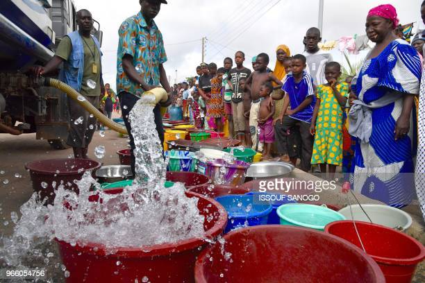 Worker of the National Office of Drinking Water distributes water to the population on June 2, 2018 in a district of Bouake, central Ivory Coast,...