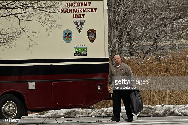 A worker of the Renaissance Meadowlands Hotel holds a plastic bag as he walks next to a incident unit truck January 31 2014 in Rutherford New Jersey...