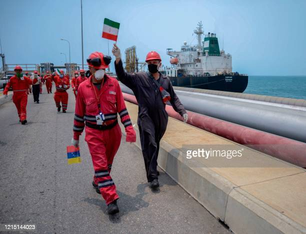 Worker of the Venezuelan state oil company PDVSA waves an Iranian flag as the Iranian-flagged oil tanker Fortune docks at the El Palito refinery in...