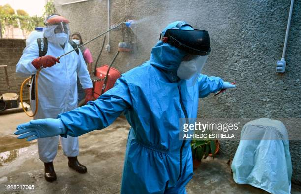 A worker of the Xochimilco local government sprays disinfectant on a coworker after disinfecting a house as a preventive measure against the spread...