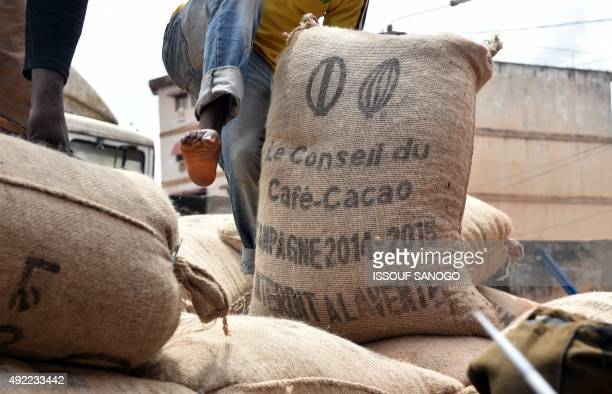 A worker off loads a hessian sack of cocoa beans on October 10 2015 in Gagnoa in southern Ivory Coast Gagnoa is the chief collecting point for a...