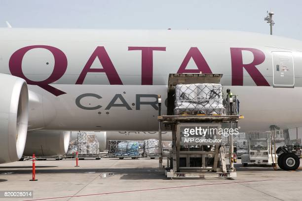 A worker offloads cargo from a Qatar Airways Cargo plane at the Hamad International Airport in Doha on July 20 2017 / AFP PHOTO / STRINGER