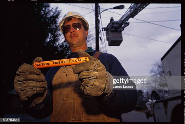 A worker on a Bell Atlantic project to provide video dial tone holds a fiber optic cable | Location Dover New Jersey USA