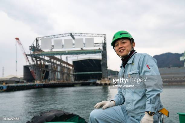 a worker on a boat in front of a large shipbuilding factory - ジャンプスーツ ストックフォトと画像