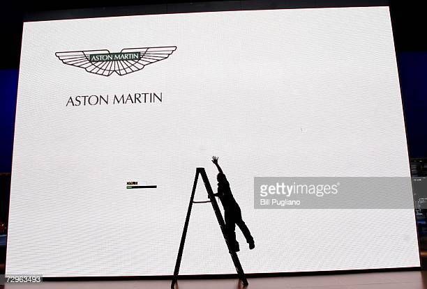 A worker on a ladder checks a giant screen at the Aston Martin exhibit at the 2007 North American International Auto Show January 8 2007 in Detroit...