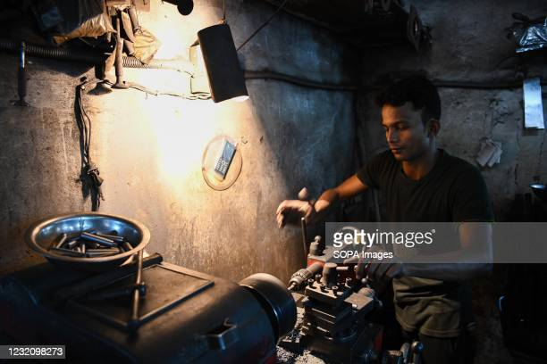Worker on a lathe machine making vehicle parts at Dholai Khal. About 200 vehicle scrap shops with thousands of workers are found in Dholai Khal where...