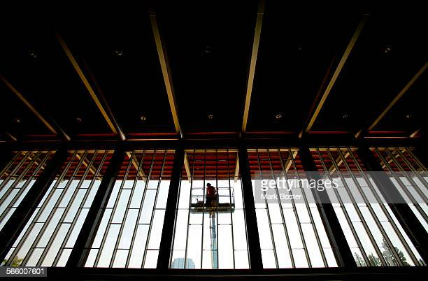 Worker on a lift makes adjustments to the windows of the Richard Neutra-designed Arboretum on the grounds of the former Crystal Cathedral July 25,...