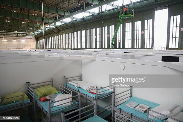 Worker on a platform stands among cubicles furnished with bunk beds ready to accommodate refugees and asylum applicants in Hangar 6 of former...