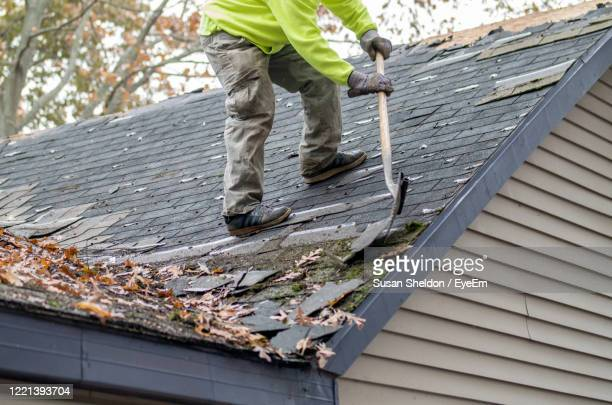 a worker on a rooftop uses a special tool to strip old shingles from a home's roof - herpes zoster fotografías e imágenes de stock