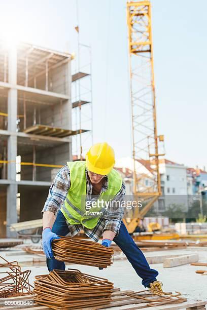 Worker on construction platform near crane