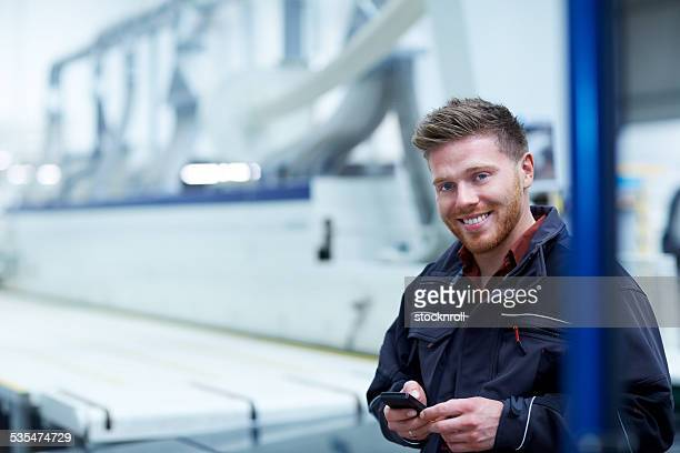 Worker on factory shopfloor with a mobile phone