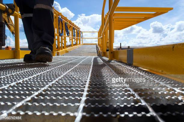 worker on oil and gas platform for produced crude oil, natural gas and water in offshore or gulf, petroleum field. industry concept of oil petroleum industry. - construction platform stock photos and pictures
