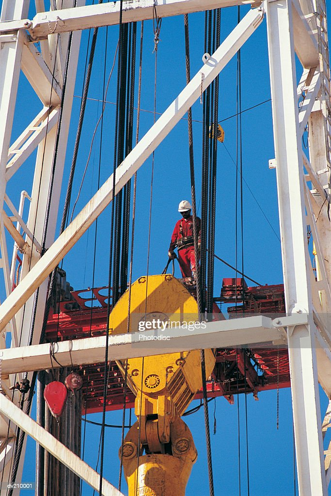 Worker on oil rig crane : Stock Photo