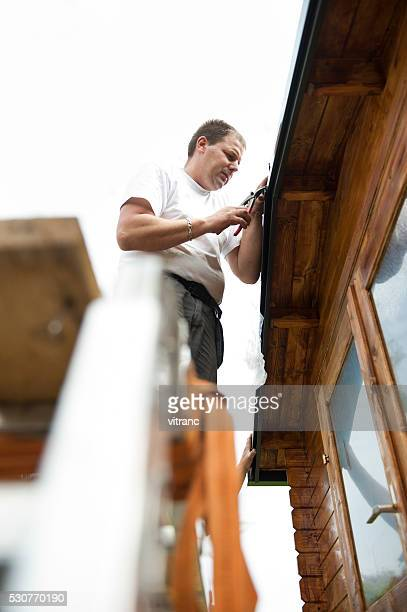 Worker on roof  installing metal tile