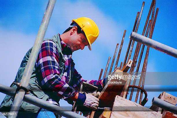 Worker on scaffolding assembling wood