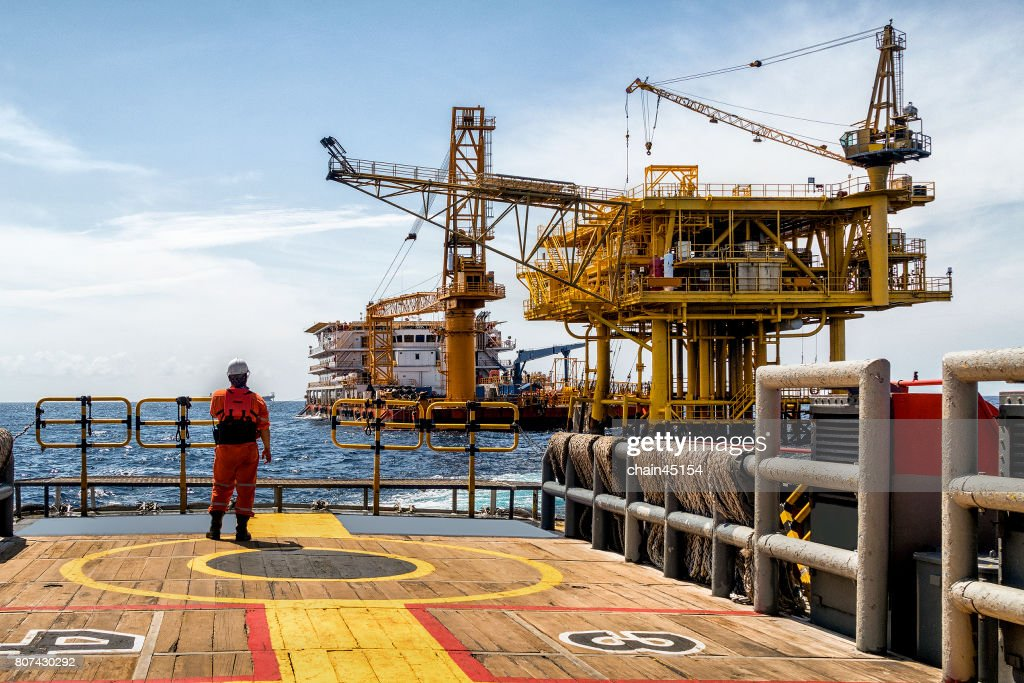Worker on the boat look at Oil and gas industrial platform in the gulf or the sea, The world energy of oil and gas company, Offshore oil and rig construction. Industry concept. : Stock-Foto
