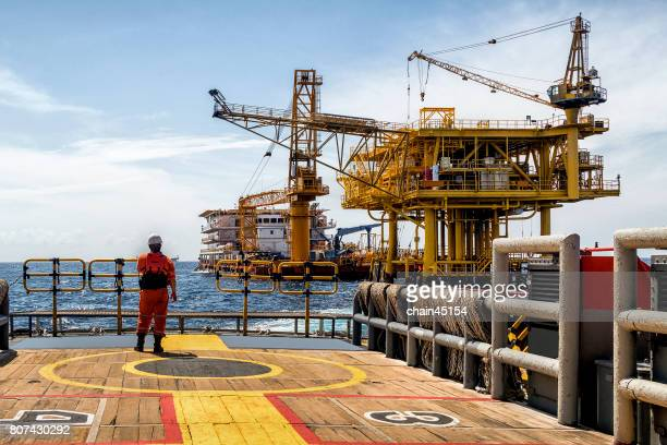 Worker on the boat look at Oil and gas industrial platform in the gulf or the sea, The world energy of oil and gas company, Offshore oil and rig construction. Industry concept.