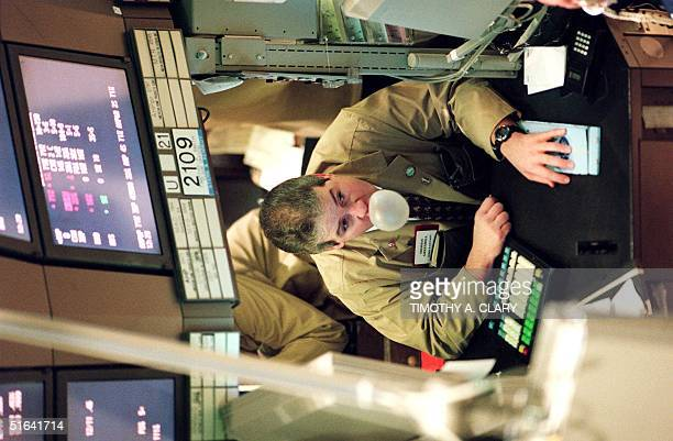 A worker on the floor of the New York Stock Exchange blows bubbles with his chewing gum as he watches the Dow drop for the fifth straight day as...
