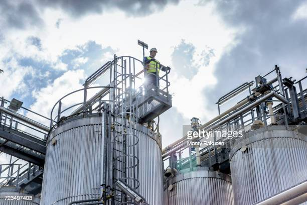 Worker on top of process plant in oil blending factory