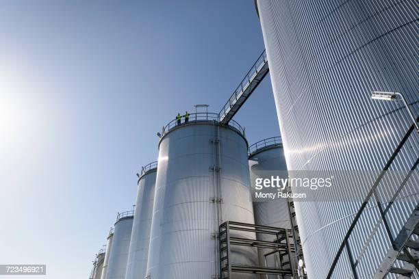 worker on top of storage tanks in oil blending factory - vorratstank stock-fotos und bilder