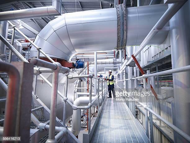 worker on walkway in gas fired power station - monty rakusen stock-fotos und bilder