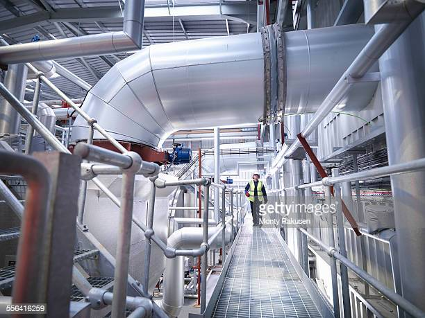 worker on walkway in gas fired power station - pipe stock pictures, royalty-free photos & images