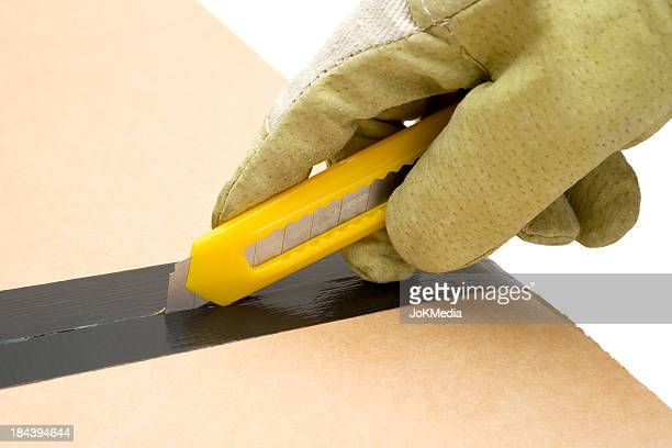 worker opening a cardboard box - utility knife stock pictures, royalty-free photos & images