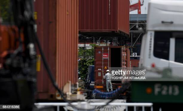 A worker opens a container at Oi container yard of the Tokyo port in Tokyo on May 18 2017 Japan has posted its longest economic expansion in over a...